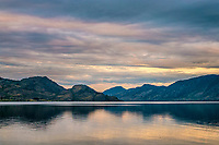 Sunset on Okanagan Lake in British Columbia, Canada. <br /> This photograph is along the shoreline of PeachLand in the Okanagan Valley. The sun's warm golden rays was producing colourful reflections on the lake, and beautiful pastel colours in the clouds over the mountains.  setting