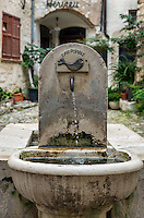 A rustic water fountain in a courtyard in the village of St Paul de Vence, Provence, France