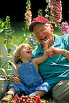 grandfather laughing and playing with toddler in garden