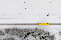People on a ski slope and ski lift and a tram travels up the mountain through the snow in Miedzybrodzie Zymieckie.