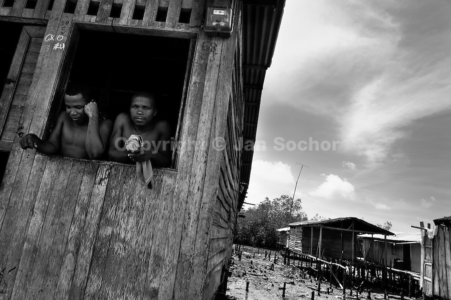 Displaced men look from the window in the stilt house village close to Tumaco, Nariño dept., Colombia, 15 June 2010. With nearly fifty years of armed conflict, Colombia has the highest number of civil war refugees in the world. During the last ten years of the civil war more than 3 million people have been forced to abandon their lands and to leave their homes due to the violence. Internally displaced people (IDPs) come from remote rural areas, where most of the clashes between leftist guerrillas FARC-ELN, right-wing paramilitary groups and government forces takes place. Displaced persons flee in a hurry, carrying just personal belongings, and thus they inevitably end up in large slums of the big cities, with no hope for the future.