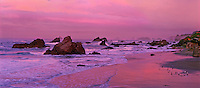 972500001 panoramic view of dawn turning the sky an alpenglow pink and warms the rocks beach sand and sea stacks along the pacific coast shoreline at harris state beach near brookings oregon
