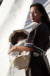 A young Native American Indian mother holding her infant in a baby cradle