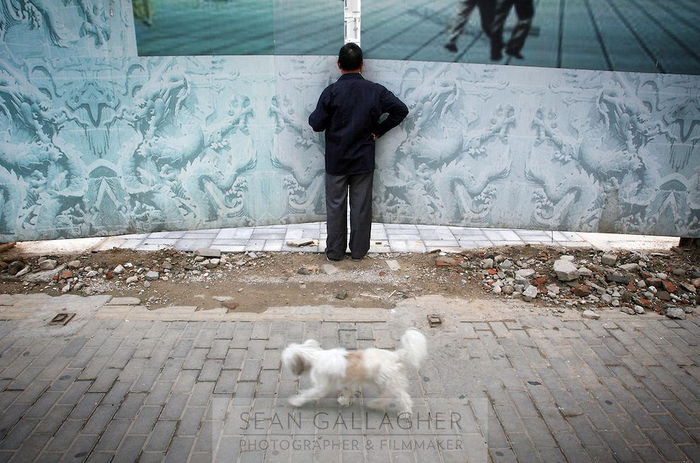 """CHINA. Beijing. A man peers through a fence, trying to catch a glimpse of the new Qianmen shopping district. In recent years construction has boomed in Beijing as a result of the country's widespread economic growth and the awarding of the 2008 Summer Olympics to the city. For Beijing's residents however, it seems as their city is continually under construction with old neighborhoods regularly being razed and new apartments, office blocks and sports venues appearing in their place. A new Beijing has been promised to the people to act as a showcase to the world for the 'new' China. Beijing's residents have been waiting for this promised change for years and are still waiting, asking the question """"Where's the new Beijing?!"""". 2008."""