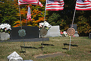 Faded Amerianc Flags blowing in the wind  at South Side Cemetery in Nottingham, New Hampshire