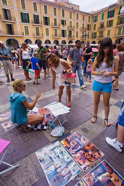 Street artist with potential clients in Plaça Major, the main square, in Palma de Mallorca in the Balearic Islands, Spain.