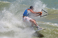 An extreme wakeboarder rides a wake at a lake.