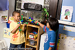 Preschool ages 3-5 two boys playing with mock weapons they made from colored connecting plastic cubes horizontal