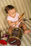 Infant development 9 month old baby girl holding wooden and metal kitchen spoons and banging them together