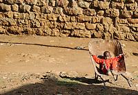 KENYA Nairobi Korogocho Slum, boy sitting hopeless in cart / KENIA Nairobi Korogocho Slum, Kind sitzt hoffnungslos in einer Schubkarre