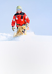 Vail Mountain's ski patroman Ben Kurtz training Vail's avalanche rescue dog, Henry, a Labroador, on a slope of fresh powder snow high atop Vail's famed back bowls.  Henry charges through the fresh, deep snow in search of a buried skier.