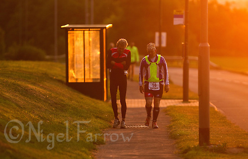 """09 AUG 2010 - LICHFIELD, GBR - Nick Holmes and Graham """"The Reverend"""" Marcussen support each other during the run as the sun rises on another day of the Triple Iron race at the Enduroman Ultra Triathlon Championships.(PHOTO (C) NIGEL FARROW)"""