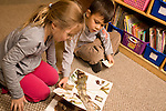 Education elementary Kindergarten reading corner boy and girl looking at picture book together horizontal