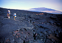 Two people hiking over lava feilds at Mauna Loa on the Big island of Hawaii