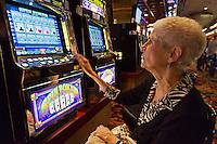 Senior woman playing a slot machines, Atlantic City, NJ, New Jersey, USA