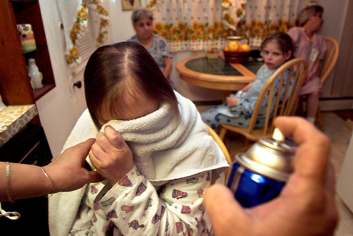 Jaime Nash gives Joyce's hair a shot of hair spray on 3/5/03, as she gets all the women ready to go out for a night of dancing at the local tavern in Waretown N.J. The girls look forward to the weekly outing and talk about it all week. Jaime Nash has four special needs women living with her and treats them all like family..05/03/03, Waretown, N.J.