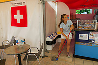 Switzerland. Canton Ticino. Tenero. Camping Campofelice.  A staff employee from the Camping is cleaning the floor with a mop at the Bar Tenda & Chico Lago. A swiss flag is hanged on the wall. The flag of Switzerland consists of a red flag with a white cross (a bold, equilateral cross) in the centre. It is one of only two square sovereign-state flags. 19.07.2018 © 2018 Didier Ruef