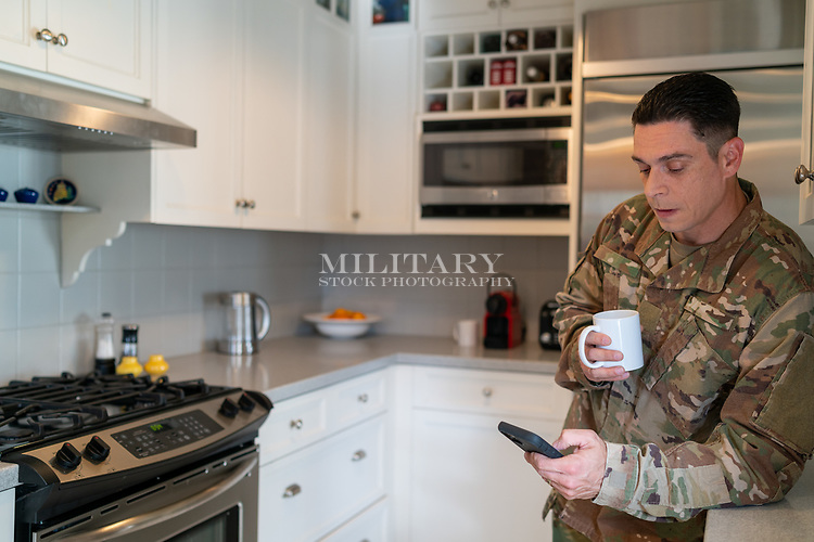 Off duty US in uniform soldier at home in his kitchen on his mobile phone, for sale as stock photography