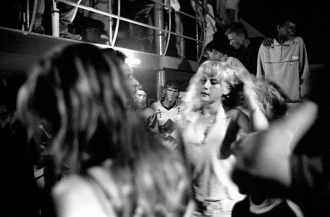 ROMANIA, Delta of Danube, Mila 23, April 2002..A girl dancing in the middle of fishermen in the nightclub of Mila 23 during the night of the resurrection..ROUMANIE, Delta du Danube, Mila 23, Avril 2002..Une fille danse au milieu des pecheurs dans la discothèque de Mila 23 la nuit de Paques..© Bruno Cogez