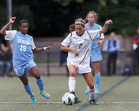 Boston College midfielder Coco Woeltz (2) dribbles as University of North Carolina midfielder Crystal Dunn (19) closes.  University of North Carolina (blue) defeated Boston College (white), 1-0, at Newton Campus Field, on October 13, 2013.