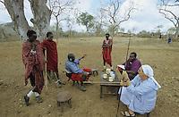 TANZANIA, Handeni, Massai, german nun holding a spear talking with Massai warrior in village / TANSANIA, Handeni, Massai Dorf, deutsche Ordensschwester Karin Kraus von der Gemeinschaft der Missionsbenediktinerinnen mit Massai Kriegern im Gespraech, in der Hand haelt sie einen Massai Speer