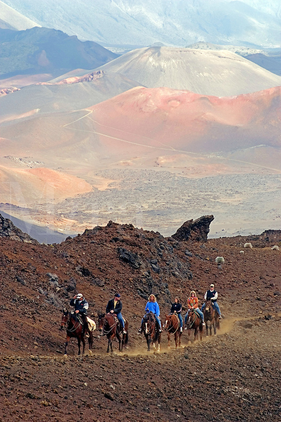 Horseback riders (MR) are working their way up sliding sands trail out of Haleakala Crater, Maui's dormant volcano. Hawaii.