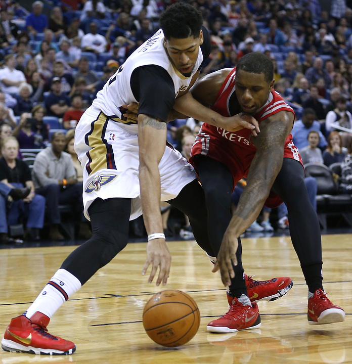 New Orleans Pelicans forward Anthony Davis, left,  and Houston Rockets forward Terrence Jones, right, go for a loose ball during the second half of an NBA basketball game Saturday, Dec. 26, 2015, in New Orleans. The Pelicans won 110-108. (AP Photo/Jonathan Bachman)