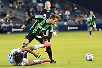 KANSAS CITY, KS - MAY 9: Tomas Pochettino #7 Austin FC with the ball and Gianluca Busio #10 Sporting KC on the ground during a game between Austin FC and Sporting Kansas City at Children's Mercy Park on May 9, 2021 in Kansas City, Kansas.