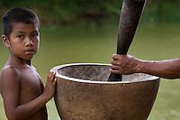 Wounaan boy helping pound the rice, Biroquera, Panama