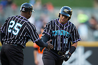 Yoan Moncada (10) of the Charlotte Knights slaps hands with third base coach Garey Ingram (25) as he rounds the bases after hitting a home run against the Norfolk Tides at BB&T BallPark on May 2, 2017 in Charlotte, North Carolina.  The Knights defeated the Tides 8-3.  (Brian Westerholt/Four Seam Images)