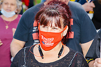 """A woman wears a red protective facemask that reads """"Trump 2020 / Keep America Great"""" and features an American flag as people gather for an anti-lockdown protest organized by the alt-right group Super Happy Fun America near the home of Massachusetts governor Charlie Baker in Swampscott, Massachusetts, on Sat., May 16, 2020. The protest was in defiance of Massachusetts orders mandating face coverings and social distancing and prohibiting gatherings larger than 10 people during the ongoing Coronavirus (COVID-19) global pandemic. The state's stay-at-home order is expected to be updated on May 18, 2020, with a phased reopening plan issued by the governor as COVID-19 cases continue to decrease. Anti-lockdown protests such as this have become a conservative cause and have been celebrated by US president Donald Trump. Many of the protestors displayed pro-Trump messages or wore Trump campaign hats and shirts with phrases including """"Trump 2020"""" and """"Keep America Great."""" Super Happy Fun America, organizers of the protest, are an alt-right organization best known for creating the 2019 Boston Straight Pride Parade."""