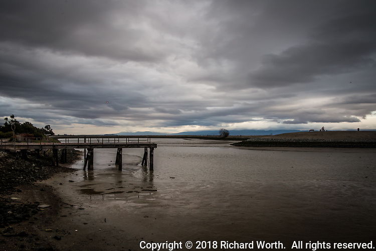 Under threatening skies, an abandoned pier steps into the low-tide muddy waters at the San Leandro Marina.