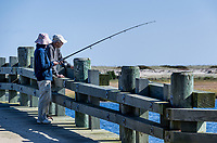 Mature couple fishing from bridge, Chappaquiddick, Massachusetts, USA.