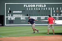 Head groundskeeper Greg Burgess of the Greenville Drive, blue shirt, directs the removal of the tarp before a game on Thursday, June 19, 2014, at Fluor Field at the West End in Greenville, South Carolina. (Tom Priddy/Four Seam Images)