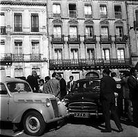 """Place Anatole France. 19 septembre 1971. Scène de reconstitution judiciaire : au 1er plan 2 voitures (une """"Juva 4"""" à gauche et une Frégate noire à droite) ; autour plusieurs groupes de personnes discutent (policiers, juge d'instruction...) ; en arrière-plan, plan d'ensemble façades immeubles. Cliché pris lors de la reconstitution, 13 ans après, du meurtre de Maurice Cathala (membre de la Convention républicaine) dans la nuit du 26 septembre 1958 par un groupe de militants communistes (assassin présumé Louis Richon photographe de presse au quotidien """"Le Patriote"""")."""