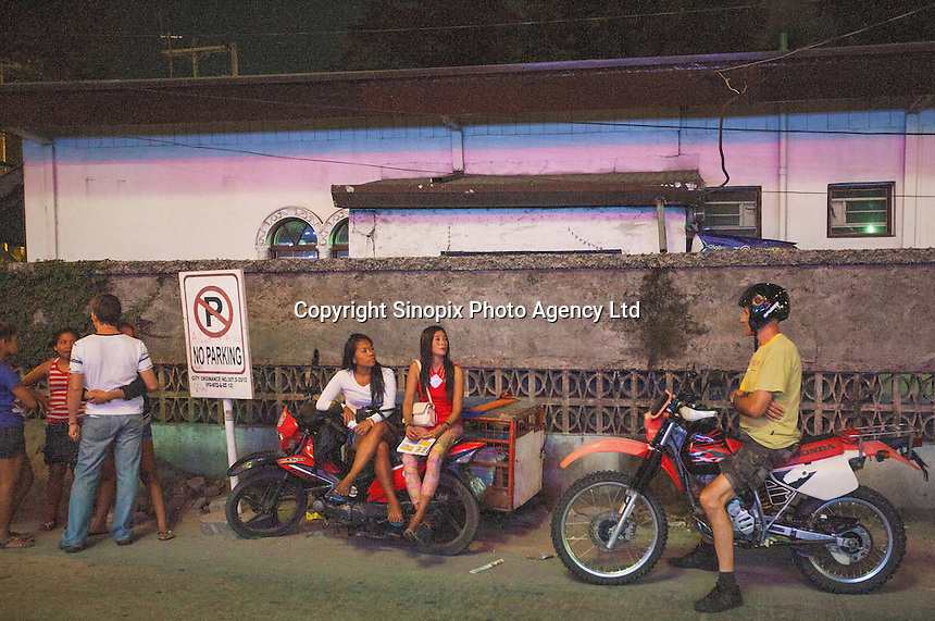 Men are seen with female prostitutes in Angeles City, Republic of the Philippines, 08 November 2014. The 'sin city', which sprung up on the fringes of a US Air Force base during the Vietnam war, has a reputation for cheap sex, and was a favourite destination for alleged murderer Rurik Jutting, who used to fly to Angeles City from Hong Kong for debauched weekends. The British banker is currently on remand at a secure facility in Hong Kong for allegedly murdering two Indonesian prostitutes in his flat whilst high on alcohol and cocaine.