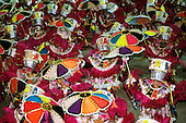 Rio de Janeiro, Brazil. Carnival procession; sambistas in long costumes with shocking pink feathers, colourful umbrellas.