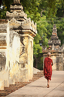 Young Buddhist monk walking through the ancient city of Ava, Inwar, Myanmar