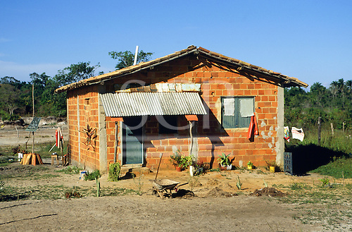 Salvador, Brazil. Small roughly built brick shack with corrugated iron porch roof and tiled main roof.