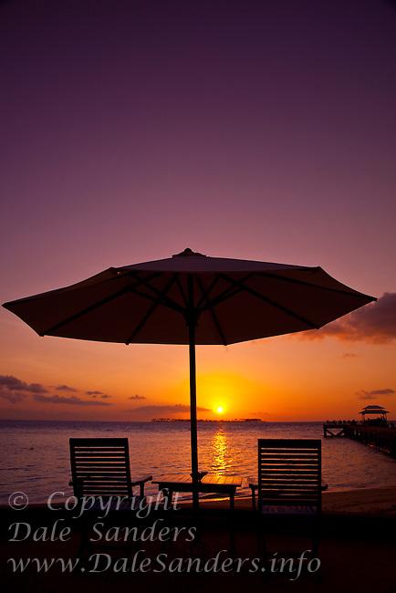 Sunset, Deck Chairs and Sun Umbrella on the beach at Wakatobi Dive Resort, Southeast Sulawesi, Indonesia.