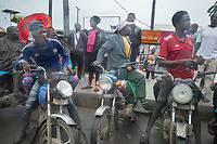 """Nigeria. Lagos. Motorcycle taxi. On a rainy day, four men seated on their motorcycle wait for customers. A motorcycle taxi, or cart bike or bike taxi, is a licensed form of transport. The taxi typically carries one passenger, who """"rides pillion"""" behind the motorcycle operator. Multiple passengers are common in Nigeria. Lagos is a city in the Nigerian state of the same name. The city, with its adjoining conurbation, is the most populous in Nigeria and on the African continent. It is one of the fastest growing cities in the world and one of the most populous urban areas. 26.06.19 © 2019 Didier Ruef"""