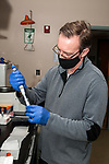 University of Rhode Island Research Assistant Professor, T.J. McGreevy, Jr., extracts mitochondrial DNA samples taken out of cheek swabs from New England cottontail rabbits trapped in Rhode Island.  In this photo he is conducting step 1 out of 8 by mixing the solution in a laboratory mixing machine.  He is adding Liquid Proteinase to the cheek swab samples inside the larger test tube.