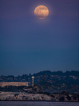 The December full moon rising over Alcatraz Island, San Francisco, CA.