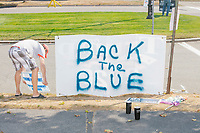 "A man puts up ""Back the Blue"" signs as alt-right organization Super Happy Fun America prepares to demonstrate against facemasks, vaccines, and pandemic closures, and in support of the reelection of President Donald J. Trump near the residence of Massachusetts governor Charlie Baker in Swampscott, Massachusetts, on Sat., Sept. 26, 2020. Super Happy Fun America is most well known for organizing the Straight Pride Parade in Boston on August 31, 2019."
