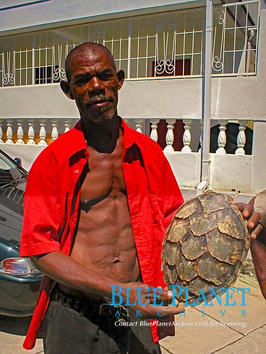 a Dominican holding a sea turtle shell, Dominica, Caribbean, Atlantic