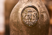 An old antique dusty wine bottle with a moulded seal on the shoulder of the bottle, probably early 19 century, seal showing a coat of arms with two animals Chateau Belingard Bergerac Dordogne France