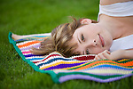 A beautiful young woman lies on a colorful knit blanket outdoors in the green grass.