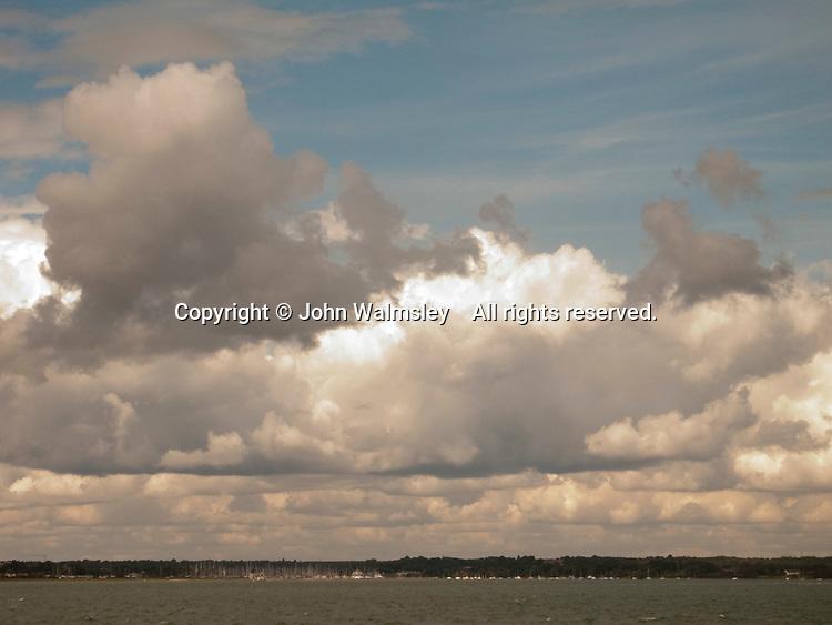 Gathering cumulus storm clouds at sea.
