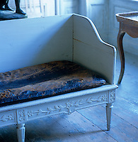 Detail of the end of a wooden sofa with a worn leather seat and carved border