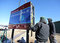 Lew Indorf (left) and Joey Weatherly, both with Ken's Signs, install Monday, February 22, 2021, a new city of Springdale city limits sign on So. Thompson Street in Springdale. The sign is equipped with solar panels that eliminated the need for power to be run to sign. Check out nwaonline.com/210223Daily/ and nwadg.com/photos for a photo gallery.<br /> (NWA Democrat-Gazette/David Gottschalk)